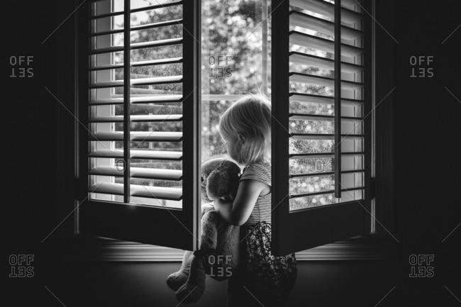 Toddler cuddling puppy at window