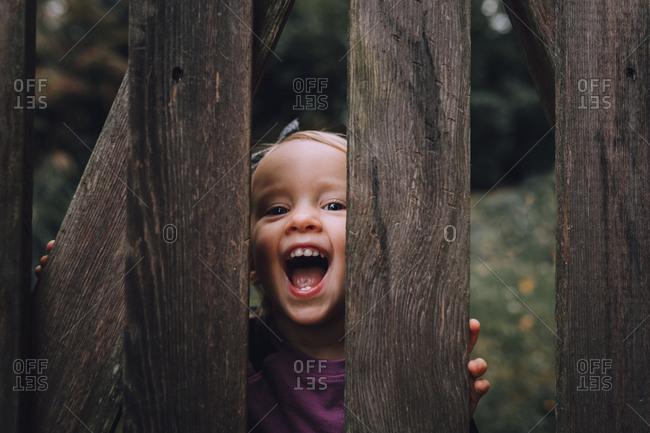 Toddler smiling through fence