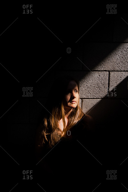 Woman stands against cement wall