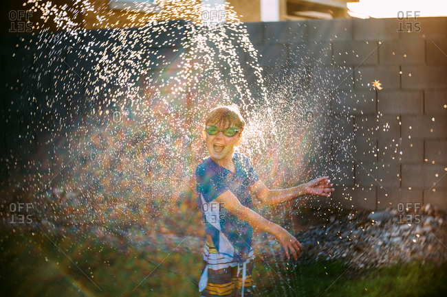 Boy stands in hose spray
