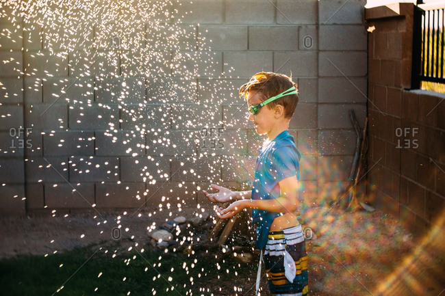 Boy stands in spray