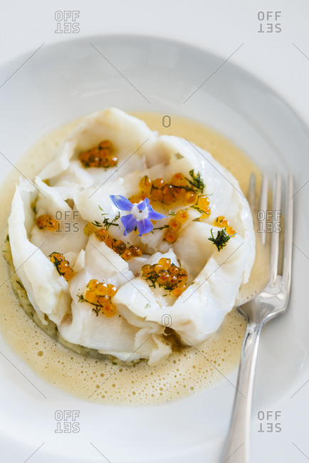 Frayed cod on crushed potatoes with trout eggs and borage flower