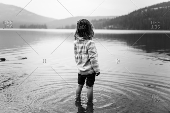 Little girl wades in lake