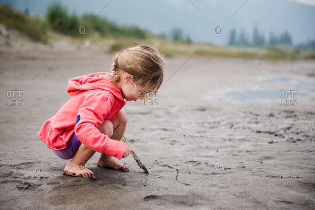 Girl draws in sand on beach