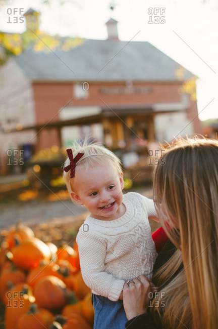 Happy little girl with mom at a pumpkin patch