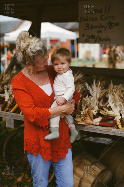 Grandmother holding grandson in front of a farm stand