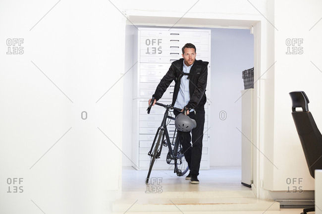 Full length of businessman with bicycle walking in creative office