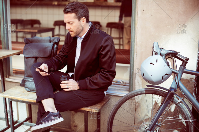 Businessman using mobile phone while sitting on bench by bicycle in city