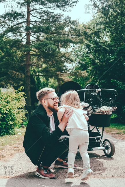 Happy man crouching while holding daughter by baby carriage on footpath at park