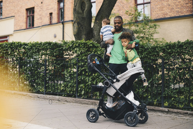 Father with children standing by baby stroller on sidewalk in city
