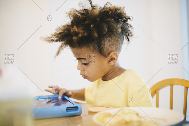 Close-up of boy using digital tablet while sitting at table
