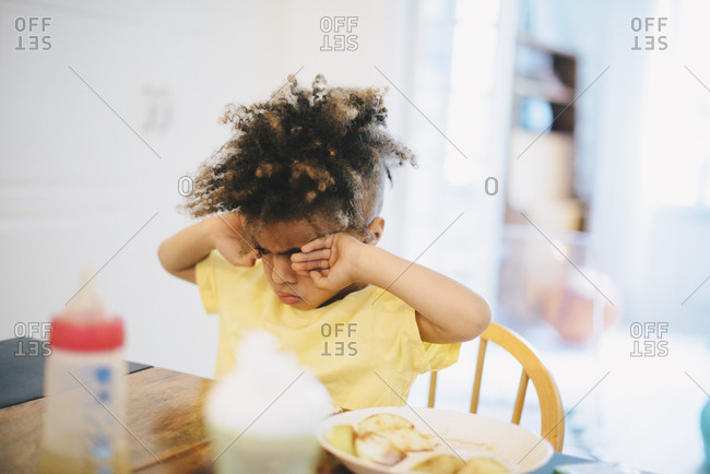 Boy rubbing eyes while sitting at table