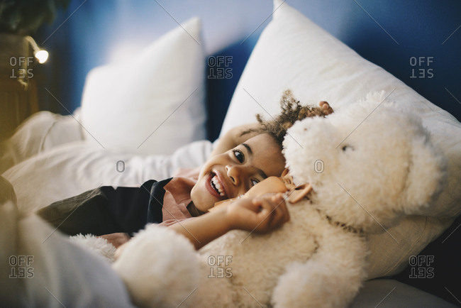 Portrait of happy boy lying with teddy bear on bed at home