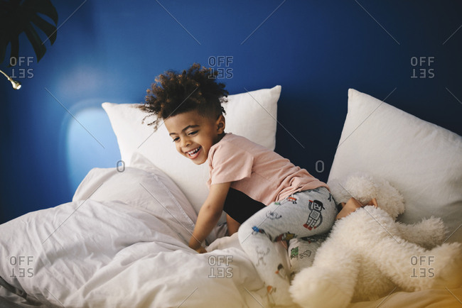 Happy boy playing with teddy bear on bed at home