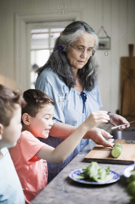 Grandmother and grandsons cutting cucumber in kitchen at home