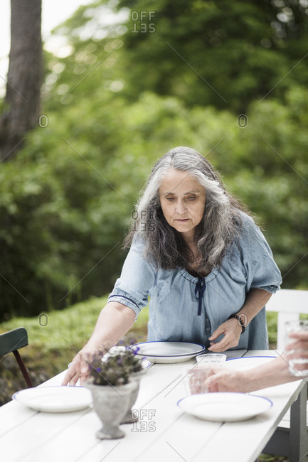 Senior couple arranging plates on table in back yard