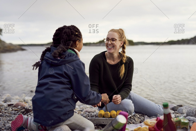Smiling woman and daughter cooking corn on barbecue grill at beach during sunset