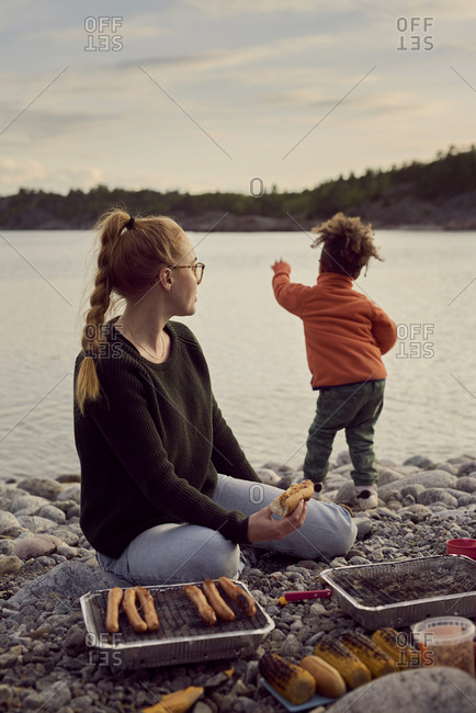 Mother sitting by barbecue grill while looking at dancing son at beach against sky