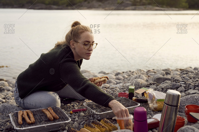 Young woman preparing food while sitting at beach during sunset
