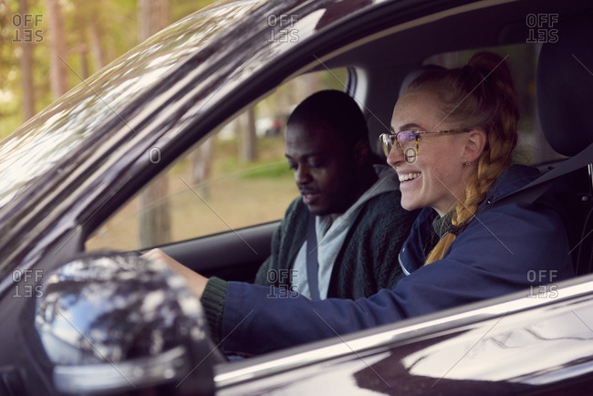 Smiling woman driving car while sitting with man