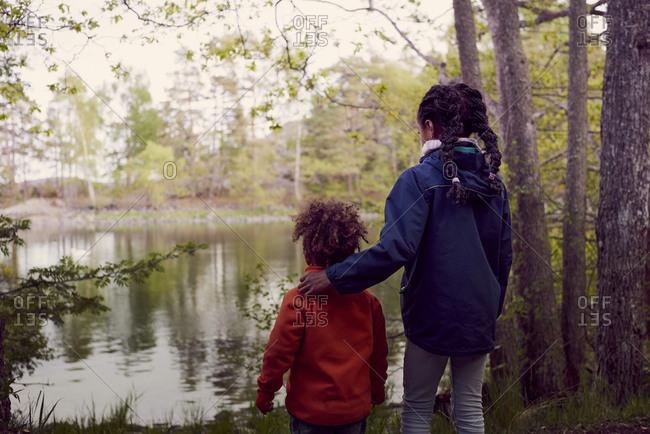 Rear view of siblings standing at lakeshore