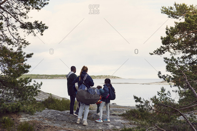 Rear view of family looking at lake against sky