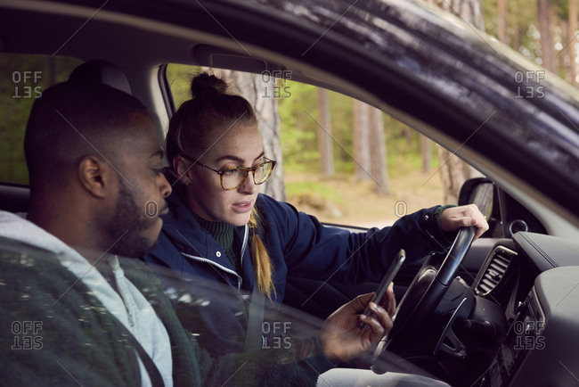 Man showing mobile phone to woman while sitting in car
