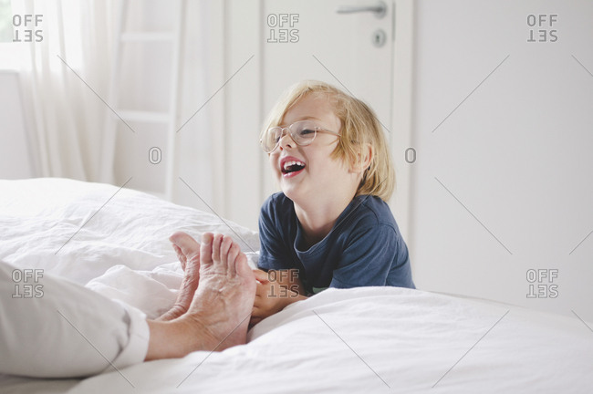 Happy grandson tickling grandmother\'s bare feet on bed at home