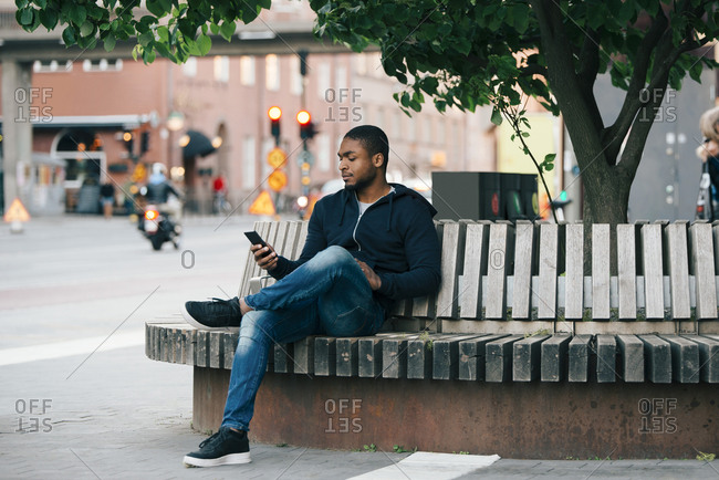 Young man using smart phone while sitting with legs crossed on bench in city
