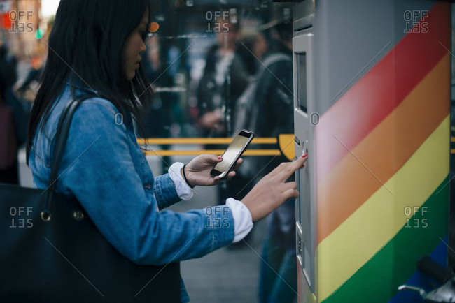 Side view of teenage girl using smart phone and ATM machine