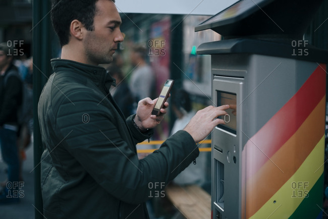 Side view of man touching ATM screen while holding smart phone
