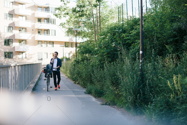 Full length of man walking with bicycle on footpath amidst railing and plants