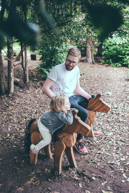 High angle view of father and daughter sitting on wooden horses at park