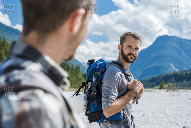 Germany- Bavaria- portrait of young hiker with backpack looking at his friend