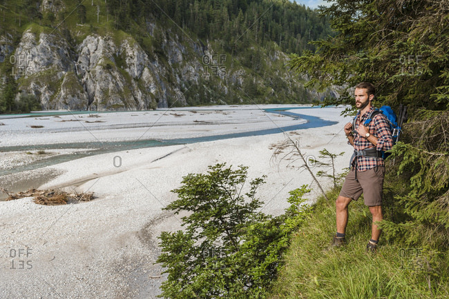 Germany- Bavaria- young hiker with backpack looking at distance