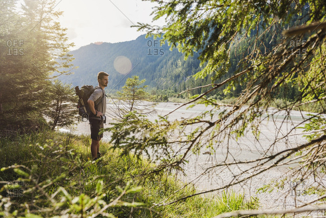 Germany- Bavaria- young hiker with backpack looking at view