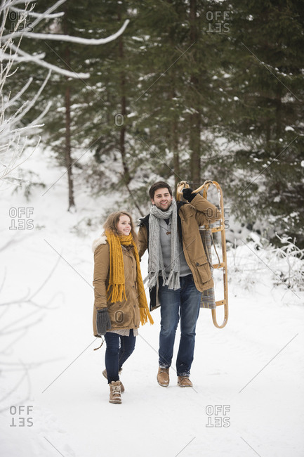 Happy young couple with sledge in winter forest