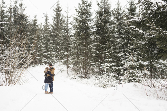 Happy young couple standing face to face in snow-covered winter forest