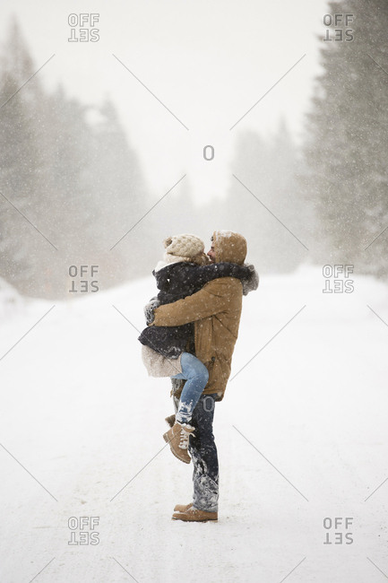 Happy young couple face to face in snow-covered winter landscape