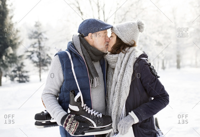 Senior couple with ice skates kissing in winter landscape