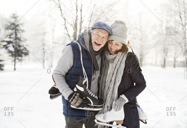 Happy senior couple with ice skates in winter landscape