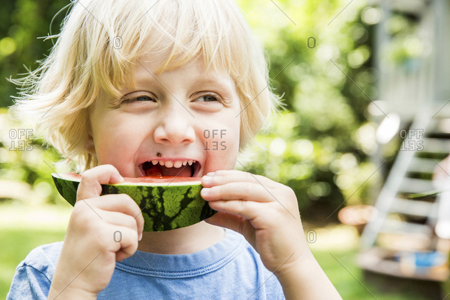 Portrait of little boy eating slice of watermelon