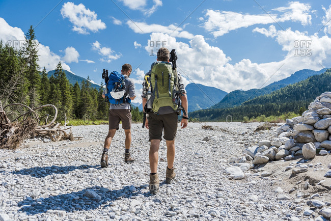 Germany- Bavaria- back view of two hikers walking in dry creek bed