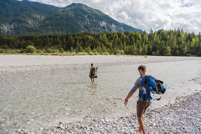 Germany- Bavaria- two hikers with backpacks crossing Isar River