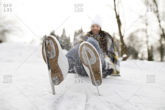 Woman with ice skates lying on snow