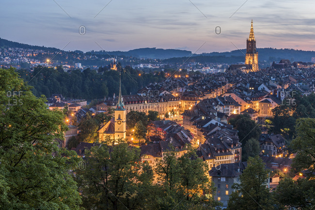 Switzerland- Bern- cityscape with lighted Nydeggkirche and minster at evening twilight