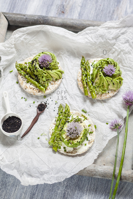 Rice cakes with cream cheese- avocado and asparagus garnished with black cumin seeds and chive blossom