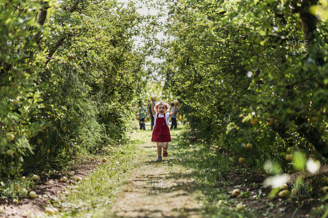 Girl running in apple orchard