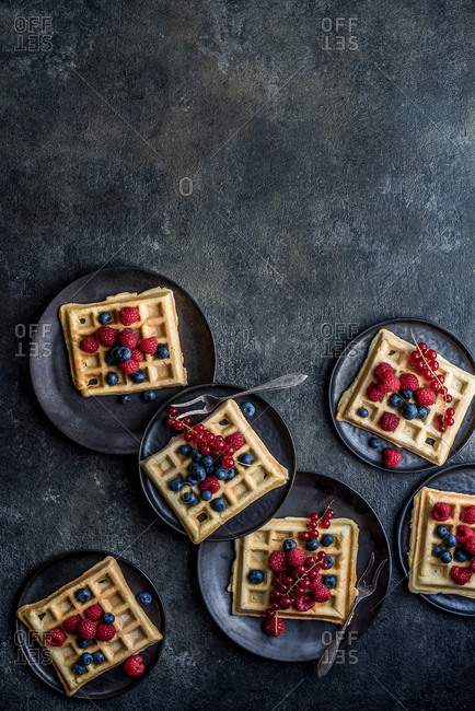 Waffles with berries on plates