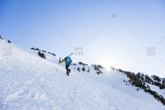 A man climbs a steep slope towards Sahale Peak, a remote mountain in the North Cascades National Park, WA while carrying his skis on his shoulder